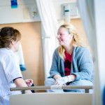 Interactie_patient en specialist praten op bed